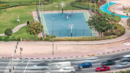 Basketball court at park in Jumeirah Lakes Towers aerial timelapse, a popular residential district towards the southern end of Dubai. Green lawn and traffic on intersection from above.