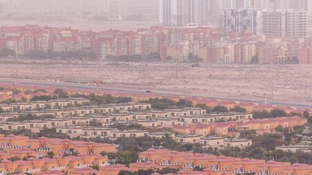 Aerial view of apartment houses, mosque and villas in Dubai city timelapse near jumeirah lake towers district, United Arab Emirates. Top fiew from skyscraper with traffic on highway Stock fotó