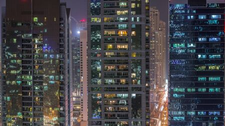 Residential and office buildings in Jumeirah lake towers district night timelapse with blinking lights in windows in Dubai. Aerial view from above with modern skyscrapers 스톡 콘텐츠