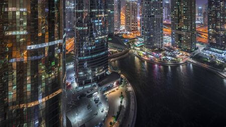Residential and office buildings in Jumeirah lake towers district night timelapse in Dubai. Aerial panoramic view from above with modern skyscrapers