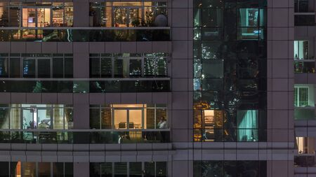 Night view of exterior apartment building timelapse. High rise skyscraper with blinking lights in windows with people moving inside. Pan left Stock Photo