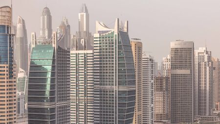 Residential apartments and offices in Jumeirah lake towers district timelapse in Dubai. Aerial panoramic view from above with modern skyscrapers 写真素材