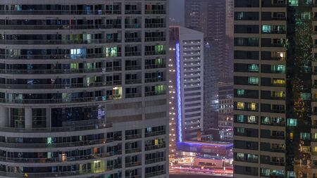 Residential and office buildings in Jumeirah lake towers district night timelapse with blinking lights in windows in Dubai. Aerial view from above with modern skyscrapers 写真素材