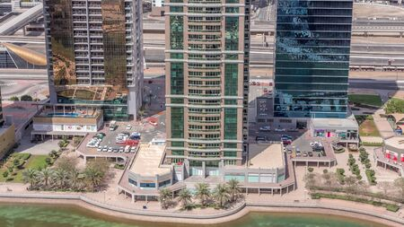 Residential apartments and offices in Jumeirah lake towers district timelapse in Dubai. Aerial view from above with modern skyscrapers with highway on background