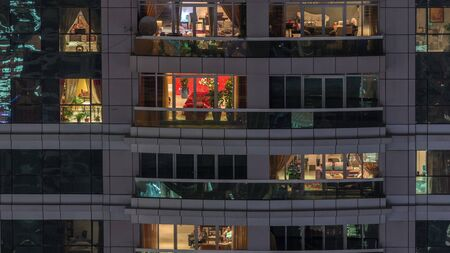 Night view of exterior apartment building timelapse. High rise skyscraper with blinking lights in windows with people moving inside. Pan right 写真素材