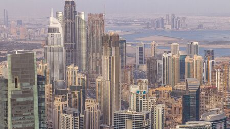 Panoramic aerial view of business bay towers and downtown in Dubai at evening timelapse. Rooftop view of some skyscrapers, canal and new towers under construction.