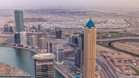 Panoramic aerial view of business bay towers in Dubai at evening timelapse. Rooftop view of some skyscrapers, canal and new towers under construction.
