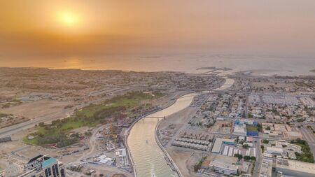 Panorama and aerial view of coastline Dubai at sunset timelapse, United Arab Emirates. Dubai water canal, sheikh zayed road, houses and villas from above 写真素材