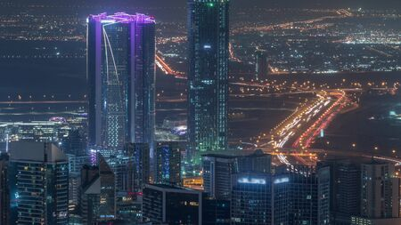 Panoramic aerial view of business bay towers in Dubai night timelapse. Rooftop view of some illuminated skyscrapers, traffic on highway and new towers under construction.