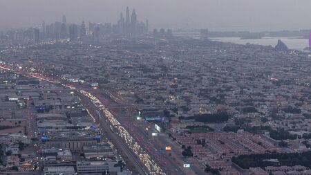 Aerial view to traffic on Sheikh Zayed road and intersection day to night transition timelapse, Dubai, United Arab Emirates. JLT and Dubai marina skyscrapers on a background. Metro line and houses.