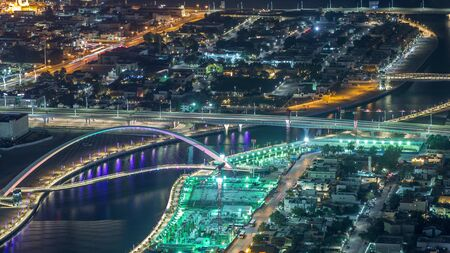 Dubai water canal with footbridge aerial night timelapse from Downtown skyscrapers rooftop. Illuminated waterfront. Floating boats and construction site with cranes 写真素材