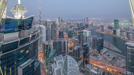 Panoramic aerial view of business bay towers in Dubai day to night transition timelapse. Rooftop view of some skyscrapers, canal and new towers under construction after sunset. Stock Photo
