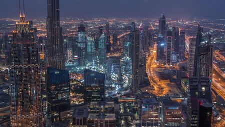Dubai Downtown skyline futuristic cityscape with many skyscrapers and Burj Khalifa aerial night to day transition timelapse. Morning panorama with modern towers and construction from rooftop before su