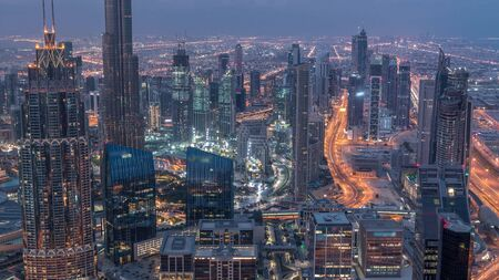 Dubai Downtown skyline futuristic cityscape with many skyscrapers and Burj Khalifa aerial night to day transition timelapse. Morning panorama with modern towers and construction from rooftop before sunrise Stock Photo