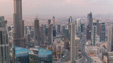 Dubai Downtown skyline futuristic cityscape with many skyscrapers and Burj Khalifa aerial timelapse. Morning panorama during sunrise with modern towers and construction from rooftop