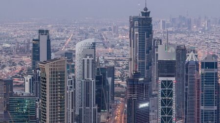 Dubai Downtown skyline futuristic cityscape with many skyscrapers and business bay aerial night to day transition timelapse. Morning panorama with modern towers and construction from rooftop before su 写真素材
