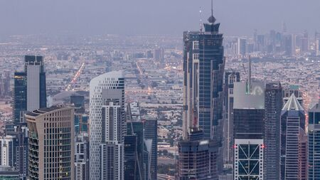 Dubai Downtown skyline futuristic cityscape with many skyscrapers and business bay aerial night to day transition timelapse. Morning panorama with modern towers and construction from rooftop before sunrise Stock Photo