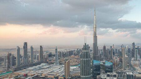 Dubai Downtown Skyline futuristisches Stadtbild mit vielen Wolkenkratzern und Burj Khalifa Luftnacht-zu-Tag-Übergangszeitraffer. Morgenpanorama mit modernen Türmen und Konstruktion vom Dach vor Sonnenaufgang