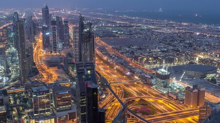 Dubai Downtown skyline futuristic cityscape with many skyscrapers and traffic on intersection aerial night to day transition timelapse. Morning panorama with modern towers and construction from rooftop before sunrise