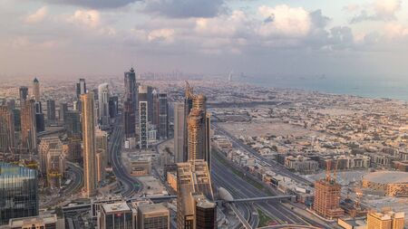Dubai Downtown skyline futuristic cityscape with many skyscrapers and business bay aerial timelapse. Morning panorama during sunrise with modern towers and construction from rooftop