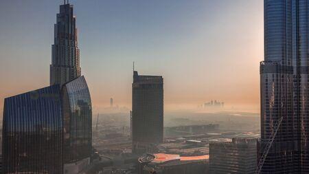 Dubai Downtown Street bei Sonnenaufgang mit viel Verkehr und Wolkenkratzern im Zeitraffer. Moderne Straßen- und Stadtgebäude mit Mall-Luftbild mit Morgendunst. Scheich Mohammed bin Rashid Blvd