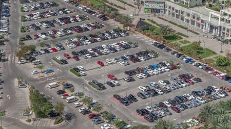 Aerial view full cars at large outdoor parking lots timelapse in Dubai, UAE. Office and recidential parking congestion and crowded parking lot with other cars try getting in and out, finding parking space.