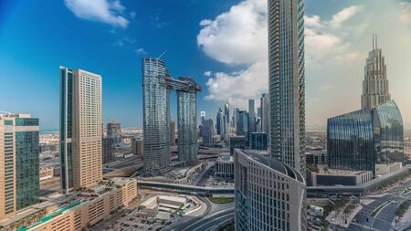 Aerial view of new towers and tall buildings with busy roads timelapse with clouds on blue sky in Dubai Downtown from above with traffic on highway, Dubai, United Arab Emirates