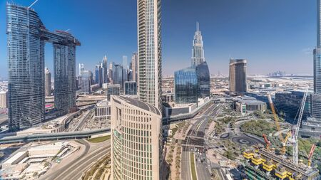 Aerial view of new towers and tall buildings with busy roads timelapse with fountains and construction in Dubai Downtown from above with traffic on highway, Dubai, United Arab Emirates