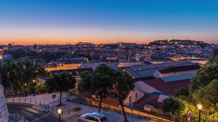 Lisbon aerial cityscape skyline night to day transition timelapse from viewpoint of St. Peter of Alcantara, Portugal. Illuminated historical buildings from above before sunrise