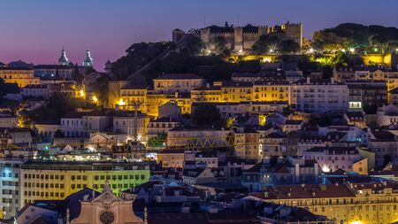 Lisbon aerial cityscape skyline night to day transition timelapse from viewpoint of St. Peter of Alcantara, Portugal. Illuminated historical buildings with Castelo de S. Jorge from above before sunrise