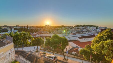 Sunrise over Lisbon aerial cityscape skyline timelapse from viewpoint of St. Peter of Alcantara, Portugal. Historical buildings from above at morning