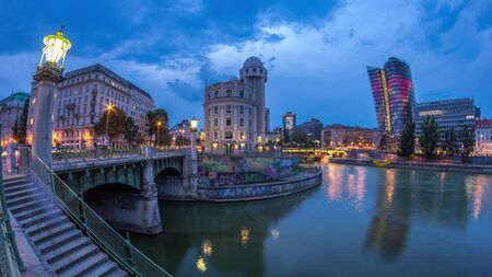 Panoramic view of Urania with other buildings and Danube Canal day to night transition timelapse in Vienna. Urania is a public educational institute and observatory