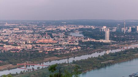 Skyline of Vienna from Danube Viewpoint Leopoldsberg aerial timelapse. Bridges over the river, skyscrapers and historic buildings at evening before sunset