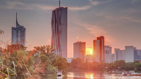 Sunset over Vienna international center skyscrapers with Kaiserwasser lake reflection view timelapse, Donaucity in capital of Austria. Colorful sky with clouds