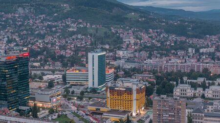 Aerial view of the southern part of Sarajevo city day to night transition timelapse. Skyline with skyscrapers and mountains from tallest tower viewpoint after sunset. Bosnia and Herzegovina, Southeast Europe.