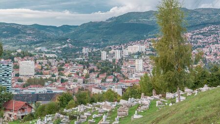 City panorama with houses and mountains from Old Jewish cemetery timelapse in Sarajevo. Skyline at evening before sunset. Cloudy sky. Bosnia and Herzegovina