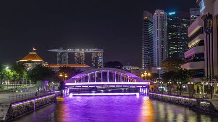 Skyline of Singapore financial district and Marina bay behind Elgin Bridge and the Singapore River night timelapse hyperlapse. Parliament building on the left side