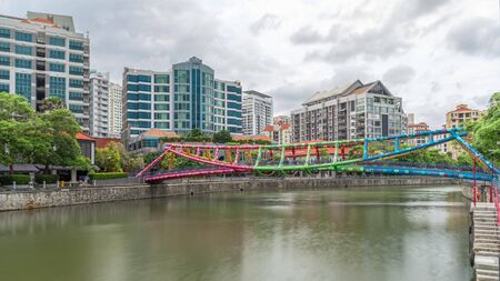 Alkaff Bridge on the Singapore River at Robertson Quay with dark gray clouds timelapse hyperlapse. Buildings reflected on a water