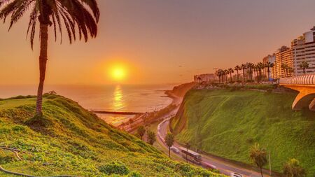 Aerial sunset view of Lima's Coastline in the neighborhood of Miraflores timelapse with orange light, Lima, Peru. Road with traffic and beach with ocean. Palm near Love park