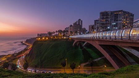 Villena Bridge with traffic and partial City view in the Background day to night transition timelapse, Lima, Peru. Aerial view with illuminated coastline and Love park