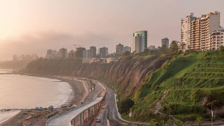 Aerial view of Lima's Coastline in the neighborhood of Miraflores during sunset timelapse with orange light, Lima, Peru. Road with traffic and beach with ocean from Husares De Junin waterfront