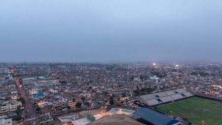 Panoramic skyline of Lima city from above with many buildings aerial night to day transition timelapse from hill. Poor houses with hills on a background. Traffic on streets. Lima, Peru