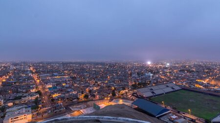 Panoramic skyline of Lima city from above with many buildings aerial night to day transition timelapse from hill. Poor houses with hills on a background. Traffic on streets. Lima, Peru Standard-Bild