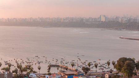 Aerial view of Lima's shoreline including the districts of Barranco and Chorrillos on background timelapse. Early morning during sunrise with many boats floating on waves in harbor. Peru