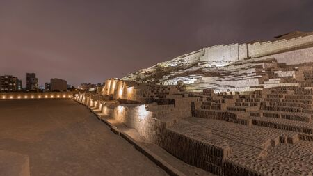 Pyramid of Huaca Pucllana day to night transition timelapse, pre Inca culture ceremonial building ruins in Lima, Peru. Clouds on a sky. Illumination is turning on Archivio Fotografico