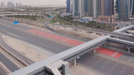 Aerial view of empty highway and interchange in Dubai after epidemic lockdown. Cityscapes with disappearing traffic on streets. Roads and lanes crossroads without cars, Dubai marina and JLT, United Arab Emirates