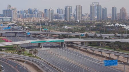 Aerial view of empty highway and interchange in Dubai after epidemic lockdown. Cityscapes with disappearing traffic on streets. Roads and lanes crossroads without cars near golf course, Dubai, United Arab Emirates