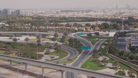 Aerial view of empty highway and interchange in Dubai after epidemic lockdown. Cityscapes with disappearing traffic on streets. Roads and lanes crossroads without cars near JLT, Dubai, United Arab Emirates