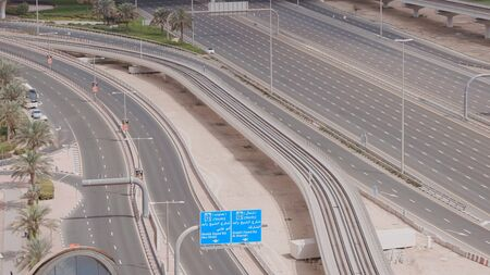 Aerial view of empty highway and interchange in Dubai after epidemic lockdown. Cityscapes with disappearing traffic on streets. Roads and lanes crossroads without cars, Dubai, United Arab Emirates