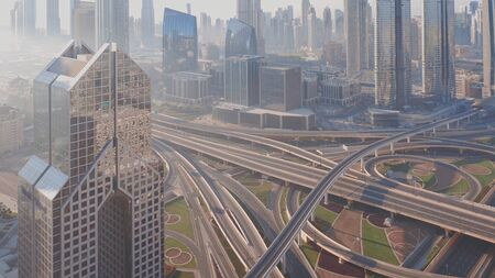 Aerial view of empty highway interchange in Dubai downtown after epidemic lockdown. Cityscapes with disappearing traffic on a bridge and streets. Roads and lanes crossroads without cars, Dubai, United Arab Emirates
